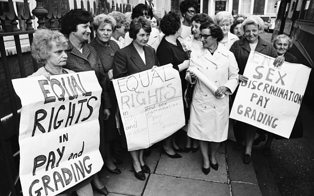 Black and white photo of female Dagenham strikers holding up signs demanding equal rights and equal pay