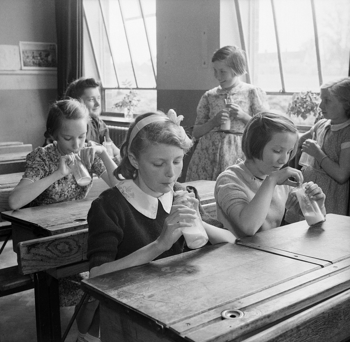 Black and white of girls at Baldock County Council School in Hertfordshire enjoy a drink of milk during a break in the school day in 1944