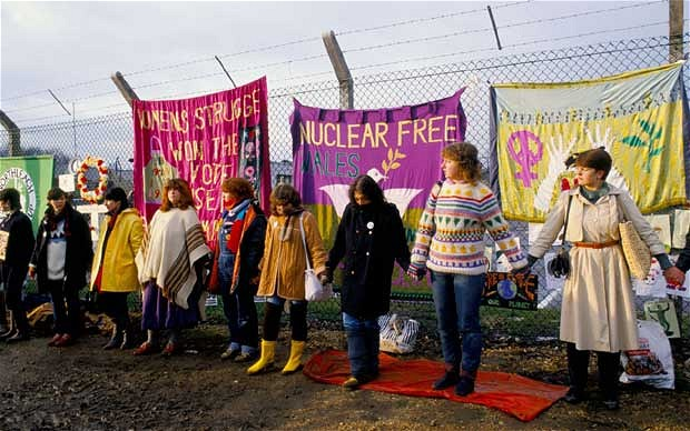 Colour photo of women holding hands in front of a fence with colourful banners reading