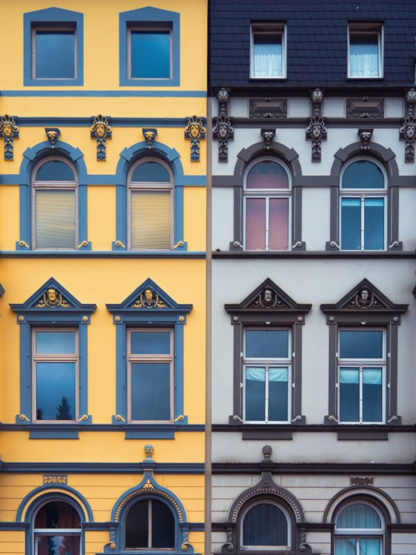 Colour photo of identical town houses painted different colours, yellow and grey