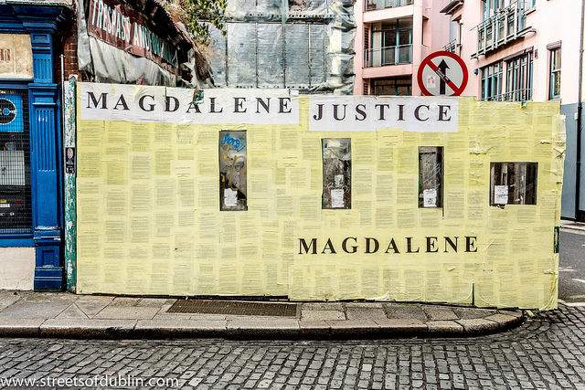 Colour photo of wall covered with papers and the phrase Magdalene Justice